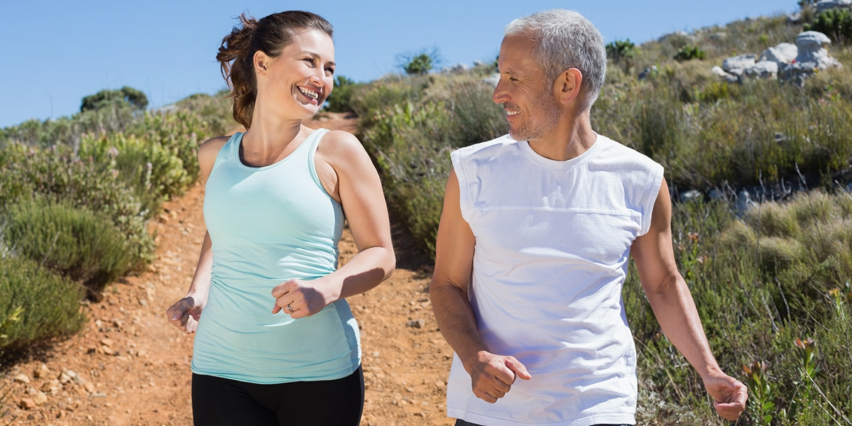 Smiling couple running in desert